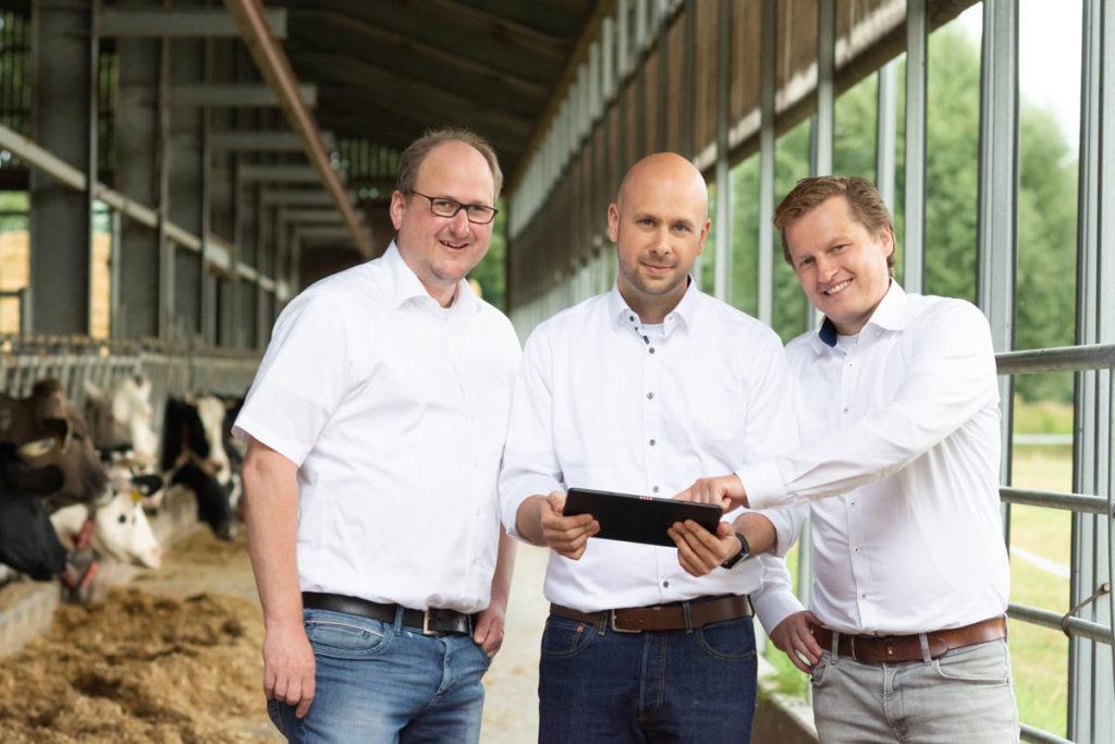 Das Team von FlexFleet mit Tablet im Kuhstall